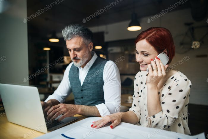 Man and woman having business meeting in a cafe, using smartphone