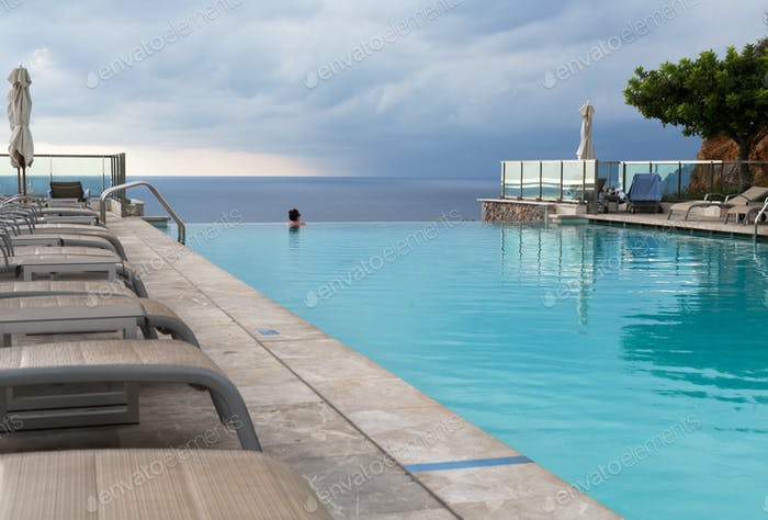 Girl in a swimming pool with sea views