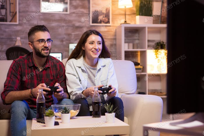 Cheerful couple playing video games at night using controllers