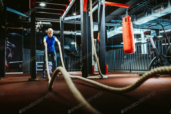 Happy fit woman with battle ropes exercise in the fitness gym