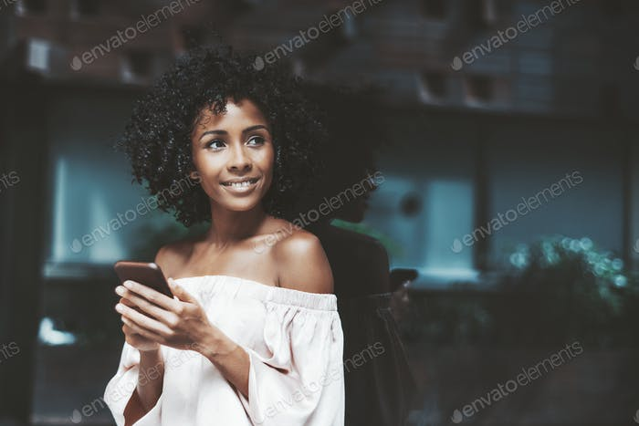 Smiling girl with cellphone outdoors