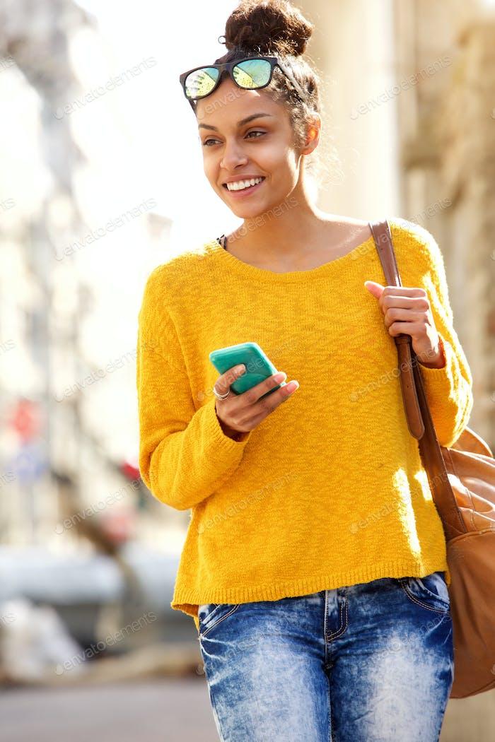 Young urban woman walking along a street outdoors
