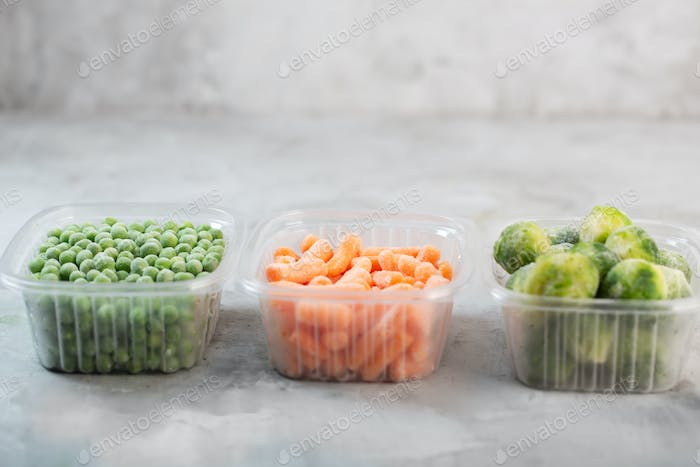 Green peas, brussels sprouts and baby carrot in the storage boxes on the concrete gray background