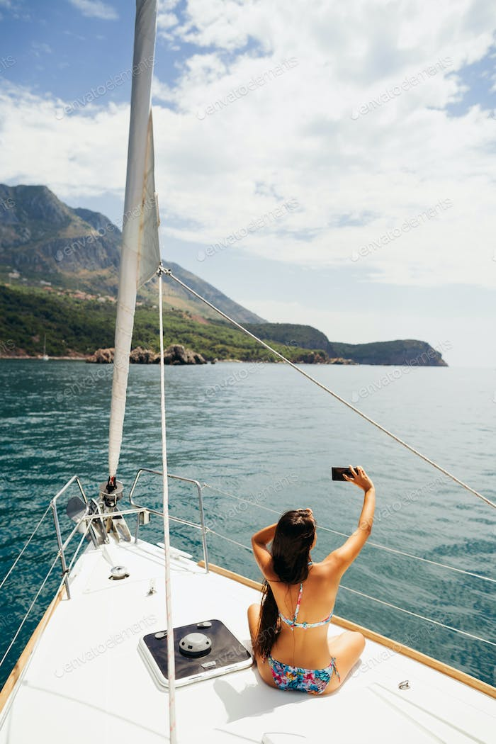 girl yachting with smartphone photograph cruise