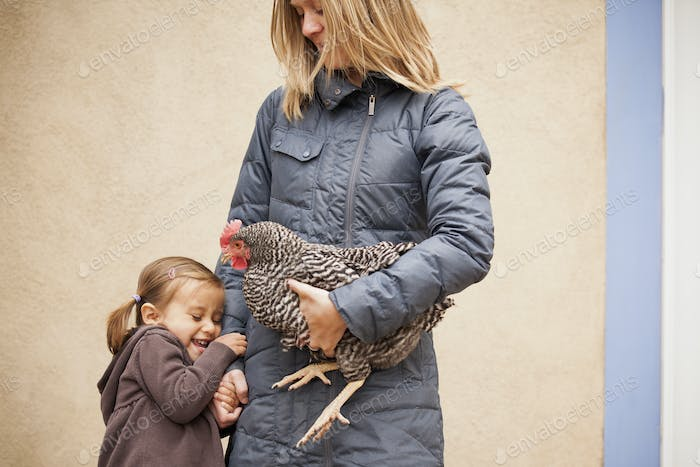 A woman holding a black and white chicken under one arm. A girl holding her other hand.