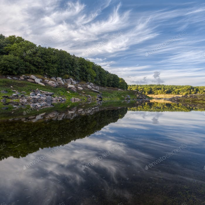 Amazing cloud formations reflected in the still waters of a rive