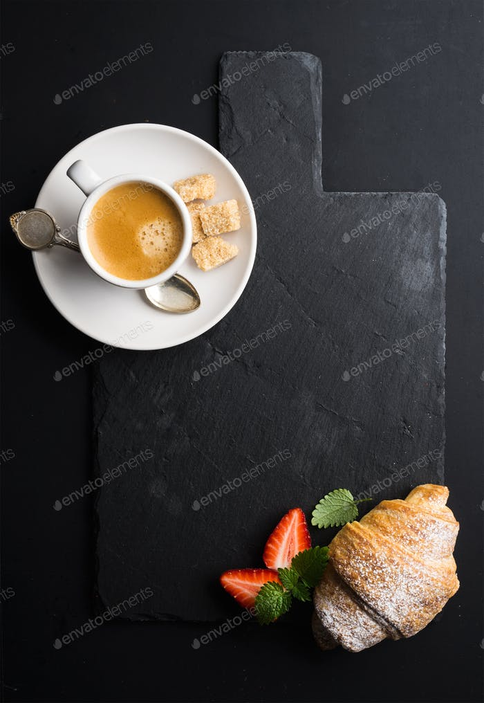 Espresso coffee cup and croissant with fresh strawberries on black slate stone board