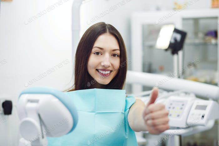 Girl showing thumbs up at a reception at the dentist
