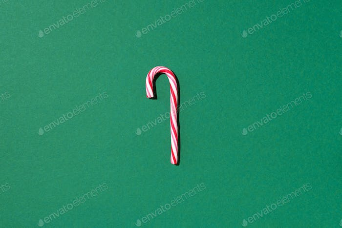 Christmas candy cane on green background with copy space. Top view. Greeting card on Christmas and