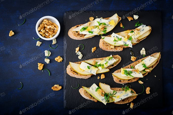 Bruschetta sandwich with pear, blue cheese, honey and nut  on a dark background. Flat lay. Top view.