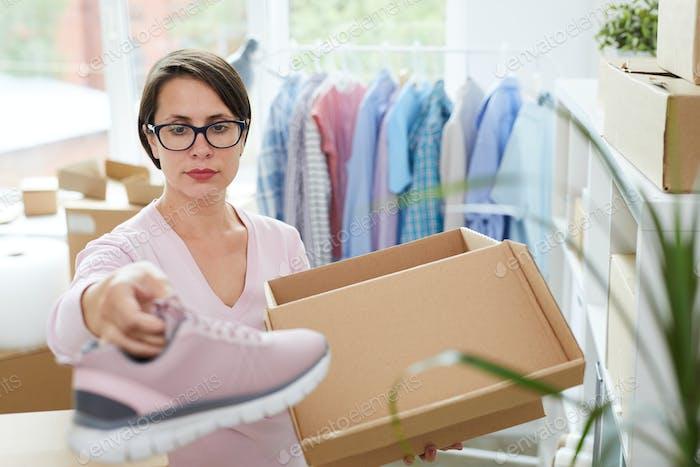 Manager von Online-Schuhgeschäft Verpackung neue Turnschuhe in Box