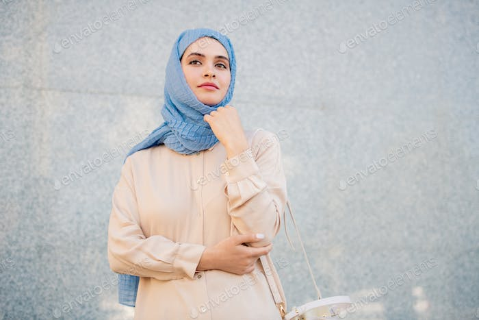 Young serene woman in hijab and casualwear standing by wall of building