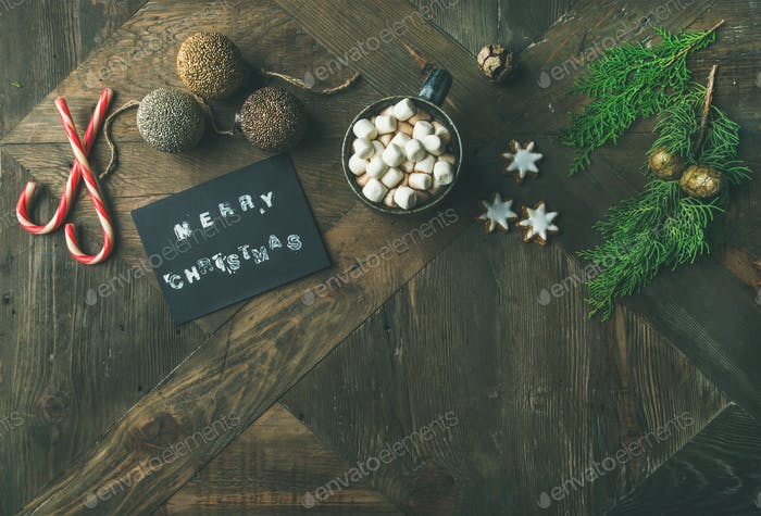 Flat-lay of greeting card, glittering toys, hot chocolate, cinnamon, cookies