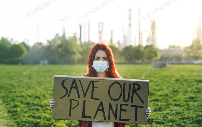 Young woman activist with placard standing outdoors by oil refinery, protesting