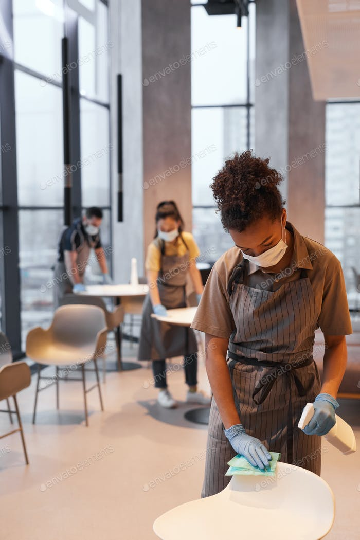 Young Woman Cleaning Cafe