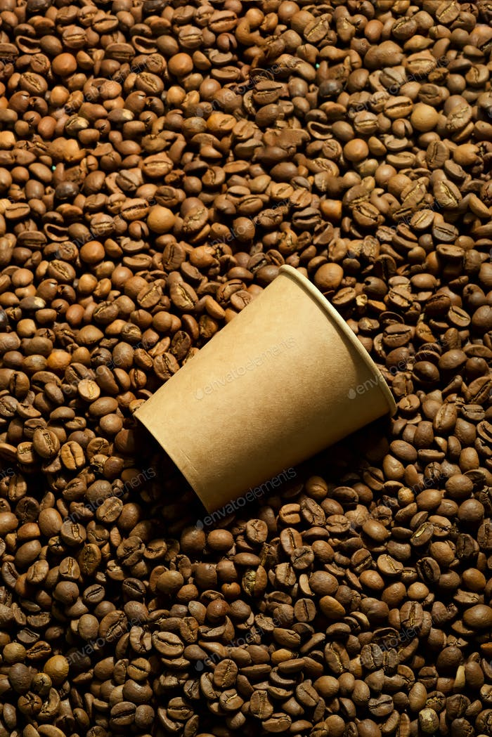 Paper cup on a coffee beans . Takeaway coffee concept