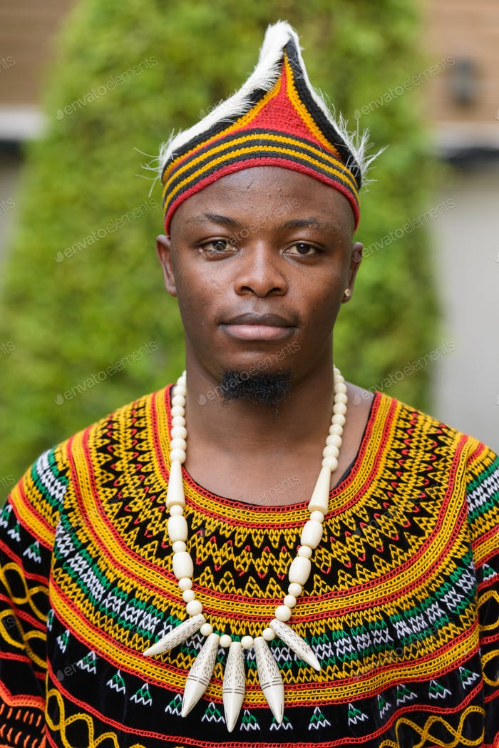 Face of young handsome African man wearing traditional clothing outdoors