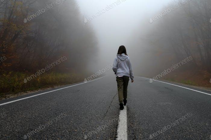 Junge Reisende, Rückansicht auf nebliger Straße im Herbstwald