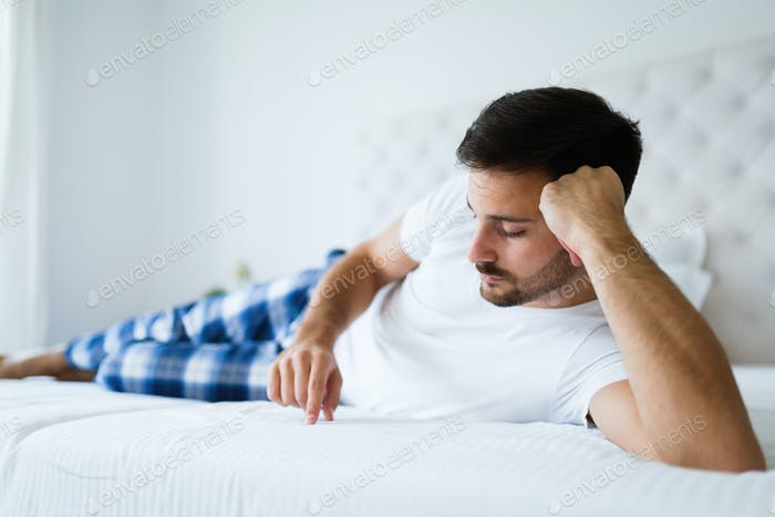 Portrait of unhappy man lying on bed