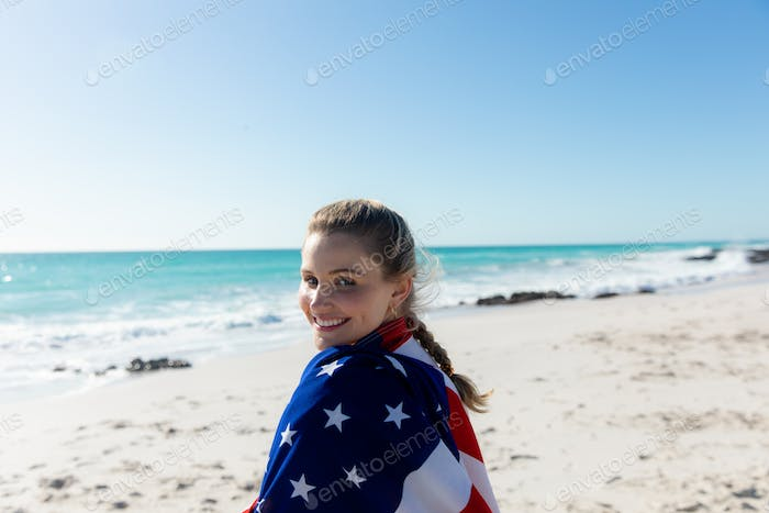 Woman with american flag at the beach