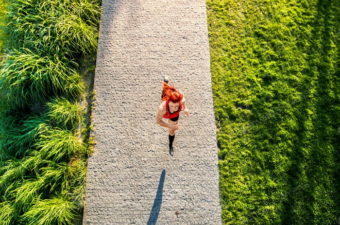 Beautiful young athlete running on a path in park.