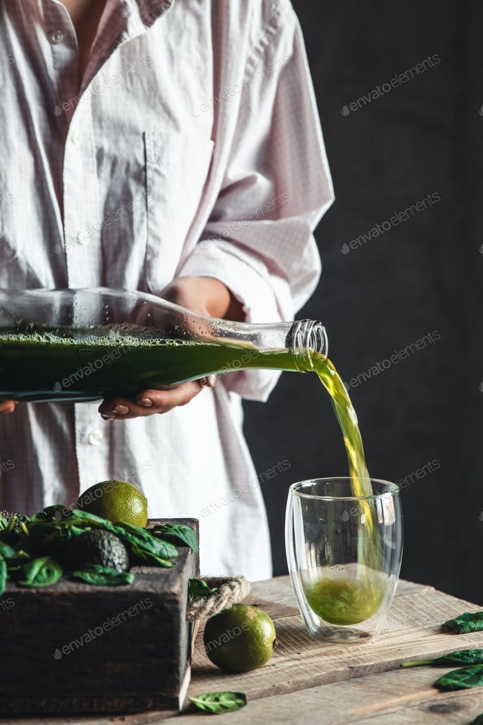 Woman pours spinach smoothie into a glass, detox, wholesome food, vegan, eco. Body cleansing