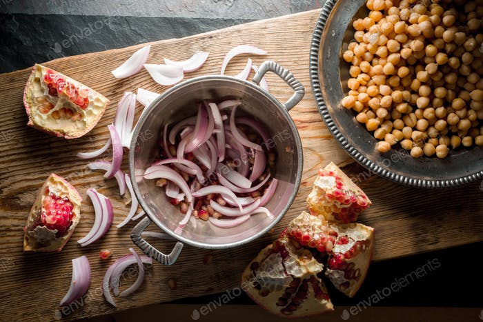 Chickpeas and onion on tin plates, pomegranate on a wooden board