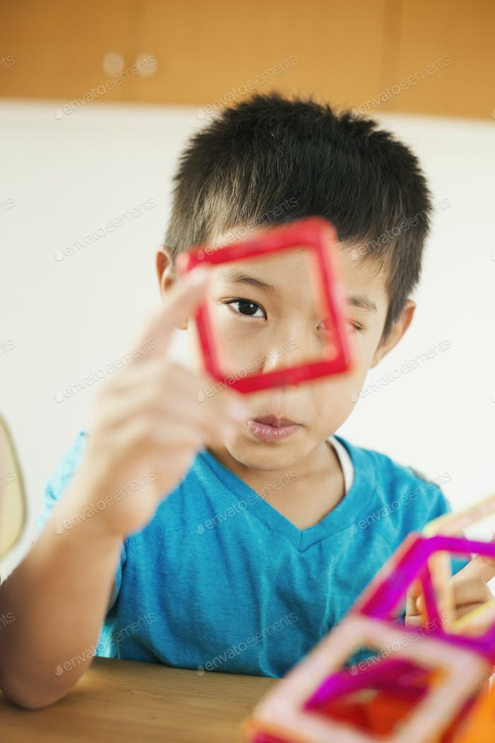 A boy playing with coloured geometric shapes.