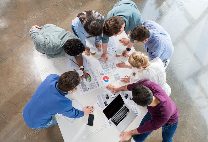overhead view of professional businesspeople discussing and brainstorming together on workplace in