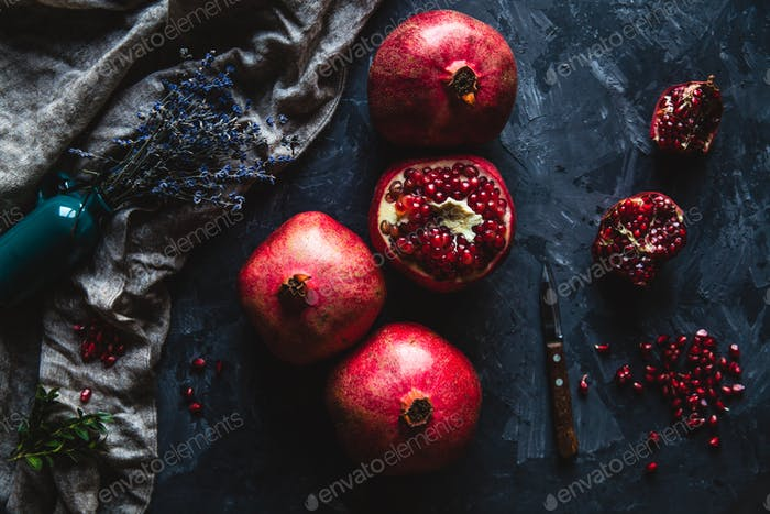 Beautiful composition of pomegranates on a dark background with a towel, healthy food, fruit