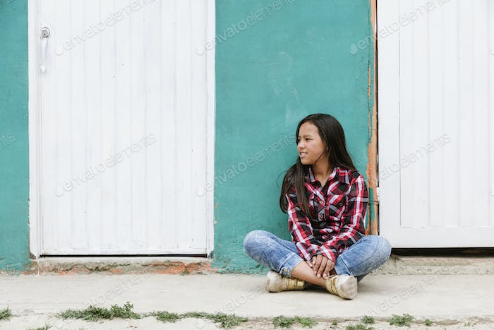 Portrait of cute latino girl in the street.