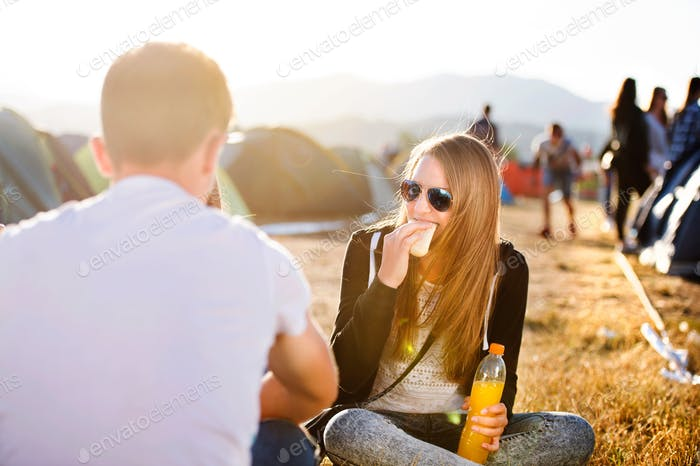 Teenagers on music festival resting, eating and drinking
