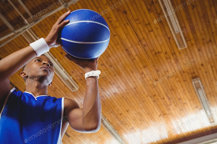 Low angle view of male teenager with basketball