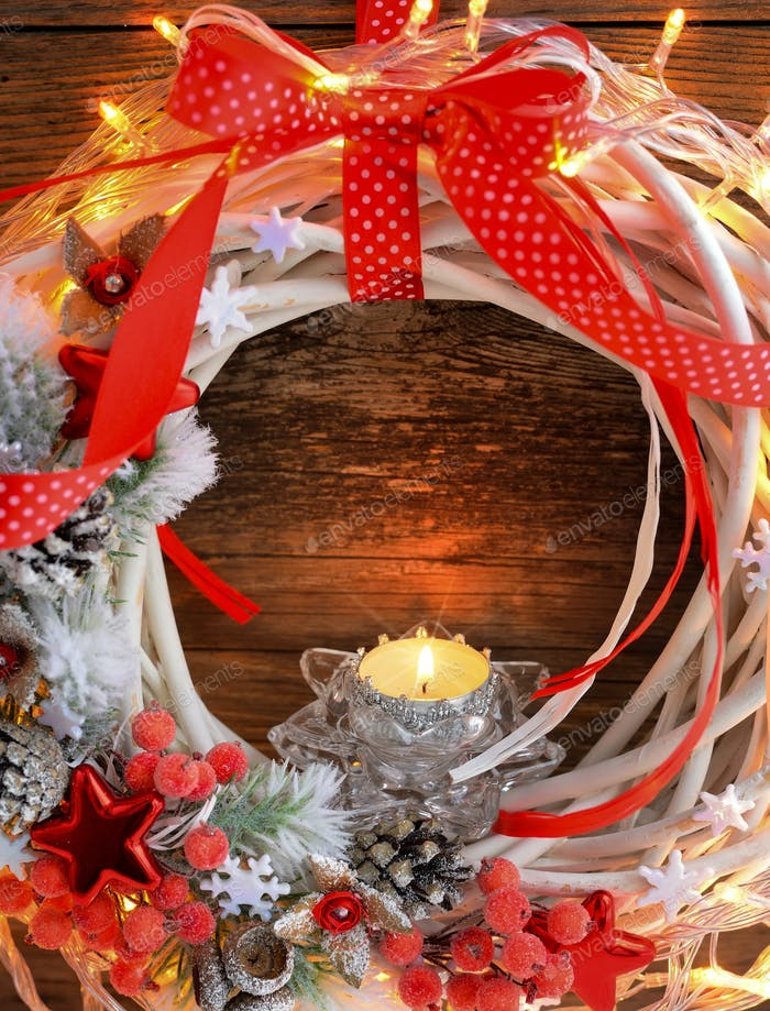 Candle with Christmas wreath and Christmas lights on a wooden ba