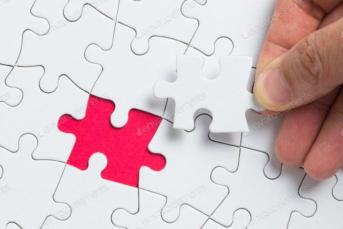 Hand putting the last piece of white puzzle for business concept or content background
