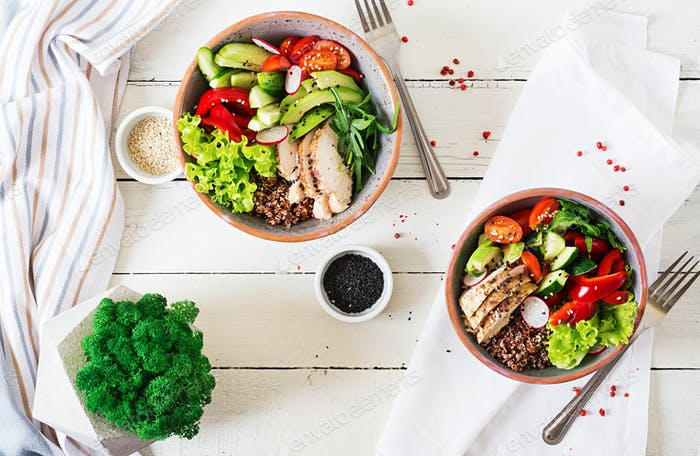 Buddha bowl dish with chicken fillet, quinoa, avocado, sweet pepper, tomato, cucumber, radish