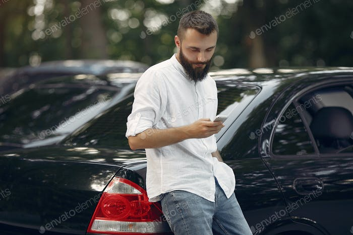 Stylish businessman standing near the car and use mobile phone