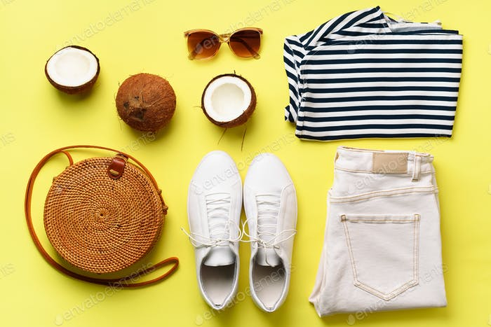 Female white sneakers, jeans, striped t-shirt, rattan bag, coconut and sunglasses on yellow