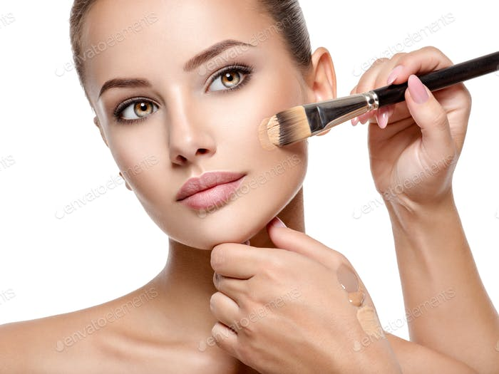 Makeup artist applying liquid tonal foundation  on the face