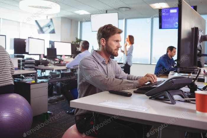 Young businessman working at desk while sitting on exercise ball