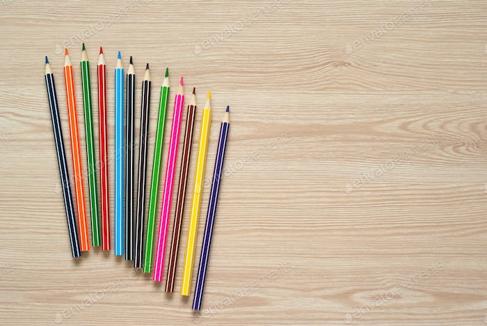 Pencils, crayons and notebook on a desk.
