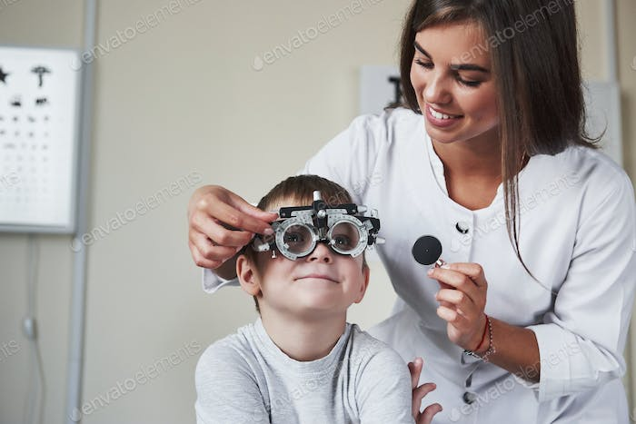 This is going fun. Doctor tuning the phoropter to to determine visual acuity of the little boy