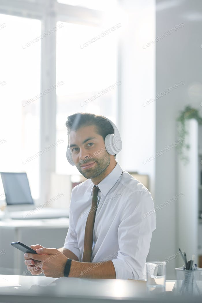 Confident young office worker in headphones using smartphone