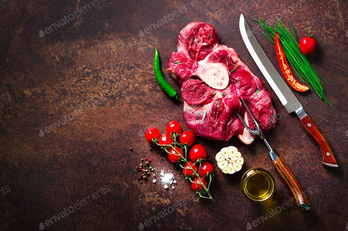 Raw fresh meat steak with cherry tomatoes, hot pepper, garlic, oil and herbs on dark stone, concrete