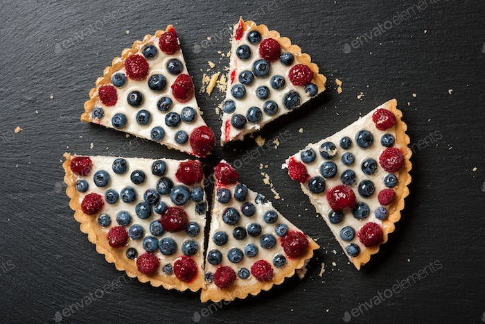 Tartlet cake with raspberries and blueberries on black stone