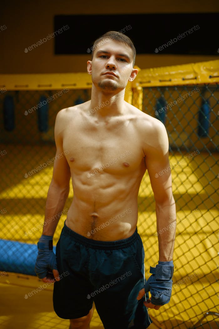 Male MMA fighter standing in a cage