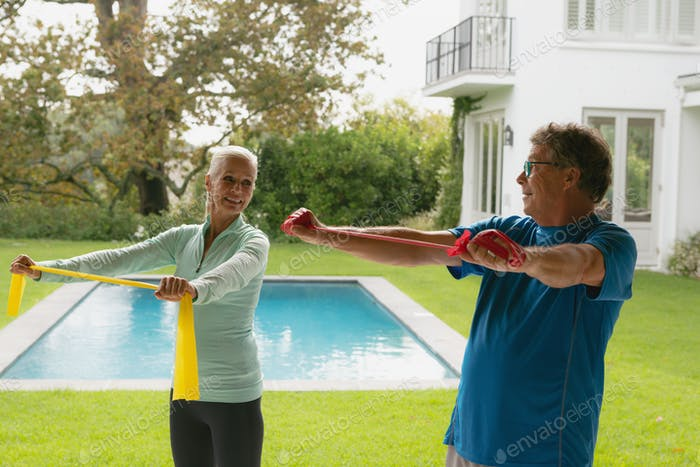 Side view of happy active senior Caucasian couple exercising with resistance band in porch at home