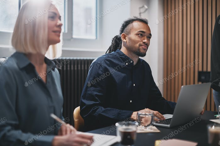 Diverse colleagues sitting together in an office meeting