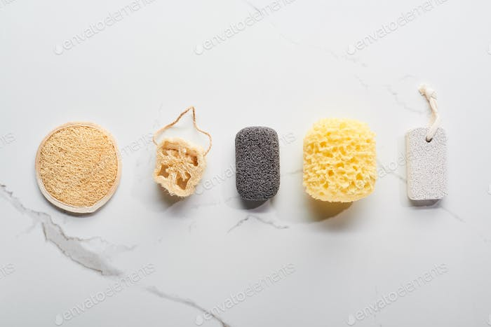 Top View of Bath Sponges And Pumice Stones on Marble Surface