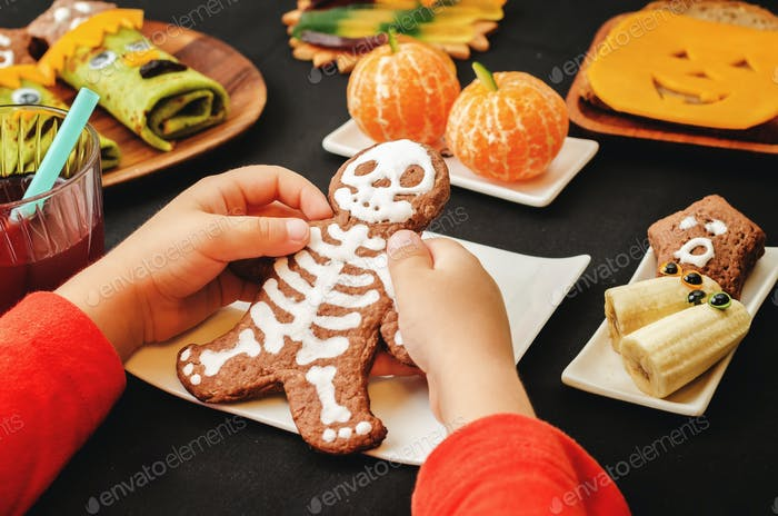 childrens hands holding cookies in the form of monsters